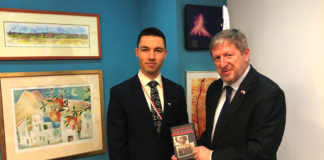 van Belostenko and Ambassador Zvi holding a DVD – a movie about the Polish Righteous Among the Nations